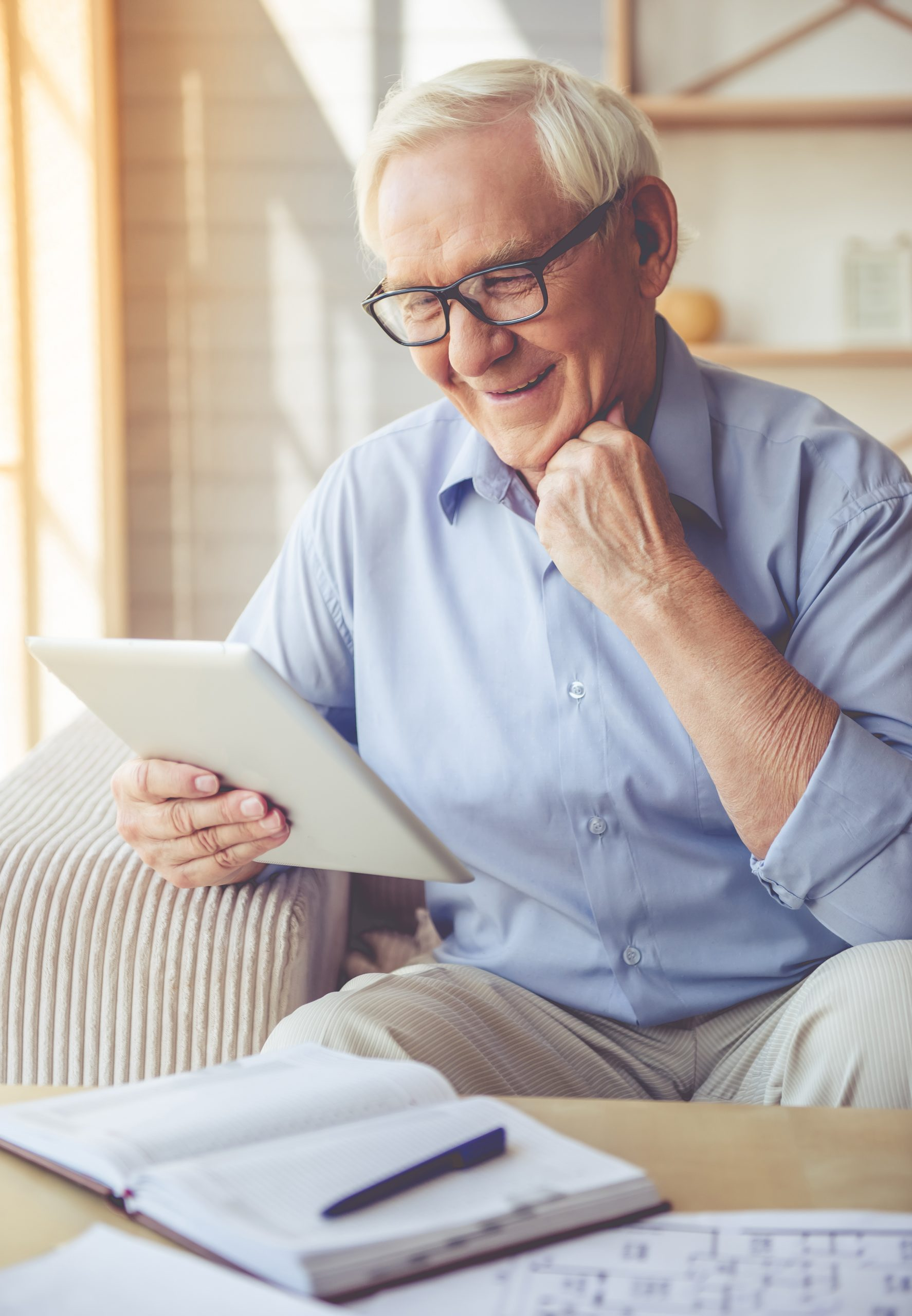 Handsome old man in eyeglasses is using a digital tablet and smiling while sitting on couch at home