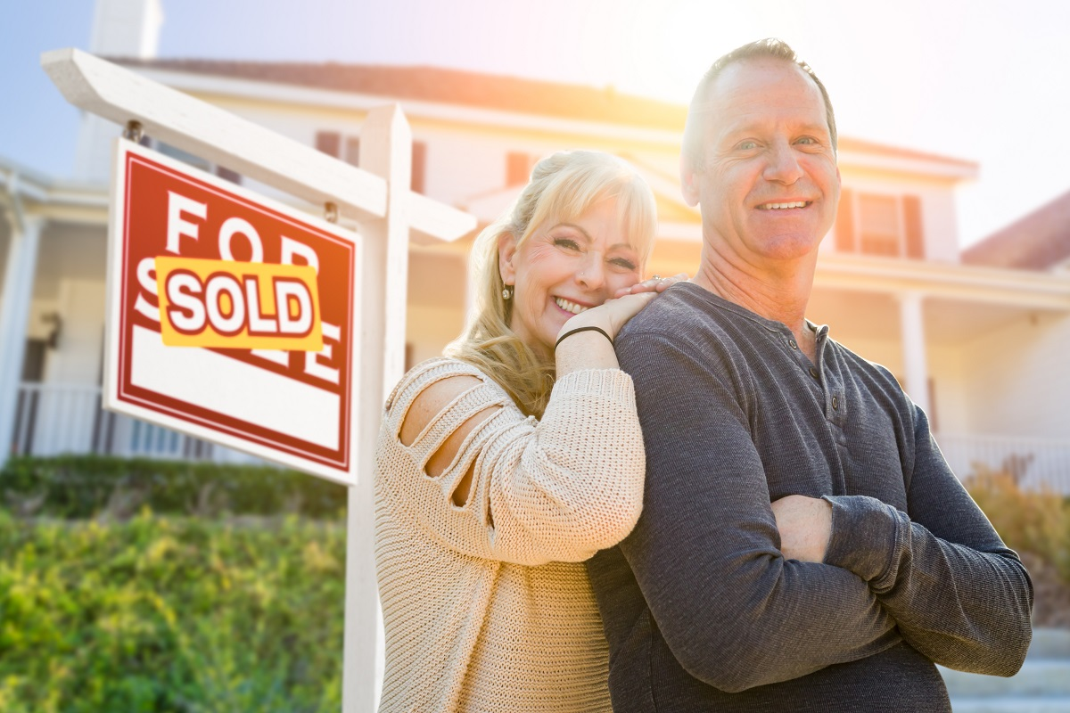 Attractive Middle-aged Couple In Front House and Sold Real Estate Sign.