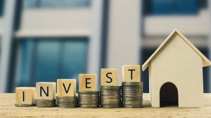 Real estate investment, Money savings for buy new home, Financial wealth management concept. Wooden block on stacked coins with wooden house model. Depicts the growth of the real estate business.